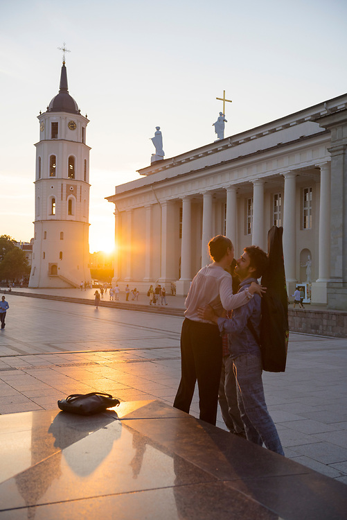 Vilnius, Lithuania - August 10, 2015: Friends greet one another with an embrace and kiss in Cathedral Square in Vilnius, Lithuania.