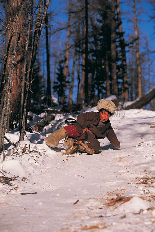 Tsaatan boy with saddle as sled<br /> Nomadic tribe with +-200 individuals left who still live in teepees<br /> Taiga Forest<br /> Northern Mongolia