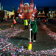 Street sweepers clean Moscow's Red Square littered with Russian flags after a party.