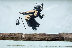 © Licensed to London News Pictures; 10/12/2020; Bristol, UK. A mural in the style of Banksy showing a woman coughing out her dentures is seen on a wall in Vale Street during the Covid-19 coronavirus pandemic in England. With England under a three-tier system Bristol is in Tier 3. With a roughly 22-degree gradient incline, Vale Street in the Totterdown area of Bristol is said to be England's steepest street. Photo credit: Simon Chapman/LNP.