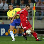 Turkey's Alpay Ozalan holds back a challenge from Brazil's Roberto Carlos