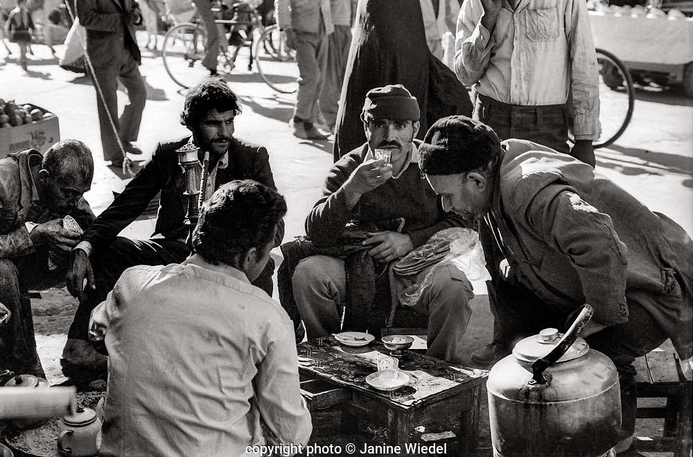 Group of men ating lunch with Hubble Bubble ( Hookah ) , kettle and mobile stove in streets of Tehran Iran 1970s