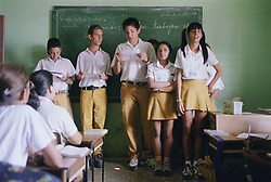 Secondary school children taking part in group presentation in classroom,