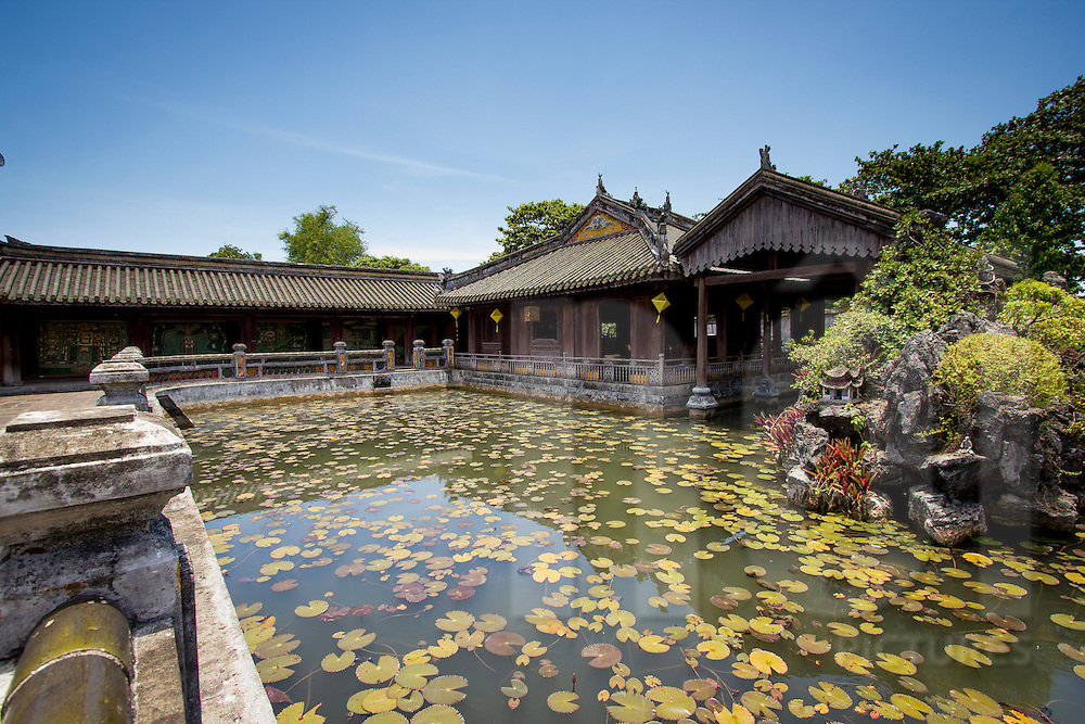 Pond full of lotus with an historic wooden building in background. Imperial citadel Hue, Thua Thien Hue, Vietnam, Asia 2012.
