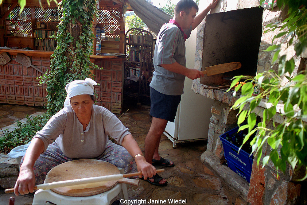 Turkish woman making bread at home with help of son in small village of Akyaka in south western Turkey.
