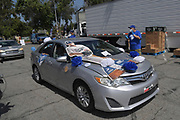 Motorists arrive at Dodger Day Drive-Thru at Belvedere Park, Tuesday, June 30, 2020, in Los Angeles. The event was hosted by The Los Angeles Dodgers Foundation, which distributed food boxes, books, sports equipment, clothing, toys and hygiene supplies to more than 1,000 registered youth from the Boyle Heights, East Los Angeles, La Puente and Monterey Park communities.