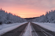 Sunset colors, snow laden trees, and a road through Alaska