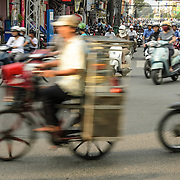 A man on a bicycle negotiates the heavy traffic of downtown Ho Chi Minh City, Vietnam.