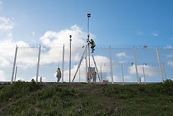 © London News Pictures. Calais, France. 15/01/16. Workers install a security camera above the fence at the Calais 'Jungle' refugee camp. French authorities are to bulldoze a 100-metre 'buffer zone' between the camp and the adjacent motorway, which leads to the ferry port. Photo credit: Rob Pinney/LNP