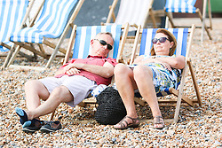 © Licensed to London News Pictures. 16/07/2015. Brighton, UK. People take advantage of the warm weather to relax and sunbath on Brighton beach. today July 16th 2015. Photo credit : Hugo Michiels/LNP