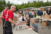 Lt. Chad Vaillancourt and Scott Smith serve Robert Jenot lunch during Woodland Heights Elementary School's Cookout and Read In on Friday afternoon.   (Karen Bobotas/for the Laconia Daily Sun)