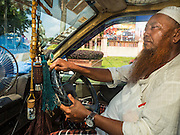 01 JUNE 2015 - KULAI, JOHORE, MALAYSIA:  MOHAMED SHAFI bin HABE, a prominent member of the Rohingya community in Kulai, Malaysia, drives through Kulai. The UN says the Rohingya, a Muslim minority in western Myanmar, are the most persecuted ethnic minority in the world. The government of Myanmar insists the Rohingya are illegal immigrants from Bangladesh and has refused to grant them citizenship. Most of the Rohingya in Myanmar have been confined to Internal Displaced Persons camp in Rakhine state, bordering Bangladesh. Thousands of Rohingya have fled Myanmar and settled in Malaysia. Most fled on small fishing trawlers. There are about 1,500 Rohingya in the town of Kulai, in the Malaysian state of Johore. Only about 500 of them have been granted official refugee status by the UN High Commissioner for Refugees. The rest live under the radar, relying on gifts from their community and taking menial jobs to make ends meet. They face harassment from Malaysian police who, the Rohingya say, extort bribes from them.       PHOTO BY JACK KURTZ