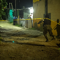 Following n murder in San Pedro Sula, crime scene tape circles the house where the body lays waiting for collection by the coroners' office.