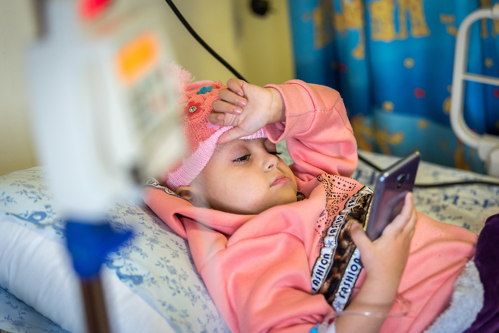 24 February 2020, Jerusalem: Four-year-old Lana, from Gaza, watches a video in the paediatric ward at the Augusta Victoria Hospital in Jerusalem. With the support of the Lutheran World Federation, Lana has come to the hospital to spend a full month there, in order to go through radiotherapy treatment for a brain tumor.