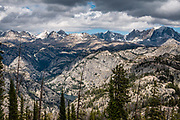 """Wind River Range seen from Photographer's Point, Bridger-Teton NF, Rocky Mountains, Wyoming, USA. The Continental Divide follows the crest of the """"Winds"""". Mostly composed of granite batholiths formed deep within the earth over 1 billion years ago, the Wind River Range is one of the oldest mountain ranges in North America. These granite monoliths were uplifted, exposed by erosion, then carved by glaciers 500,000 years ago to form cirques and U-shaped valleys."""