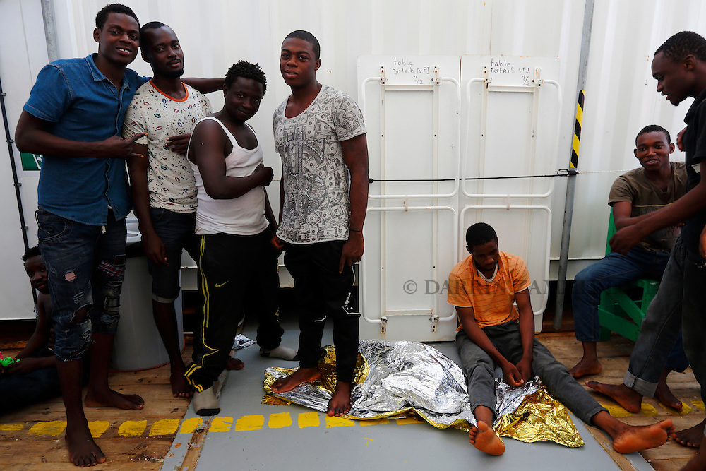 Migrants pose for a picture on board the Medecins san Frontiere (MSF) rescue ship Bourbon Argos somewhere between Libya and Sicily August 8, 2015.  Some 241 mostly West African migrants on the ship are expected to arrive on the Italian island of Sicily on Sunday morning, according to MSF.<br /> REUTERS/Darrin Zammit Lupi <br /> MALTA OUT. NO COMMERCIAL OR EDITORIAL SALES IN MALTA