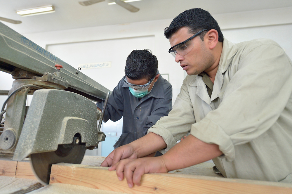 Instructor Ishamis Abu Mhasin helps a student learn to use a saw in a woodworking class in the Vocational Training Center in Gaza City, Gaza. The center is run by the Department of Service for Palestinian Refugees of the Near East Council of Churches, a member of the ACT Alliance, and funded in part by the Pontifical Mission for Palestine.