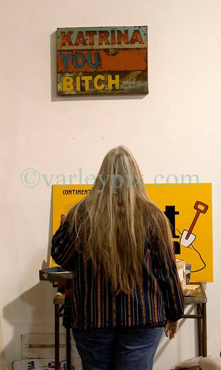 07 Jan, 2006.  New Orleans, Louisiana. Post Katrina.<br /> Barrister's art gallery in New Orleans hosts a show titled 'Katrina you bitch.' A lady stops to look at the sign. <br /> Photo; Charlie Varley/varleypix.com