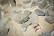 Portuguese Summer. Young couple enjoy the sun bath between the rocks at Azenhas do Mar beach in Sintra.
