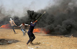 April 13, 2018 - Khan Younis, Gaza Strip, Palestinian Territory - A Palestinian protester uses a slingshot to hurl stones towards Israeli security forces during clashes in a tent city protest where Palestinians demand the right to return to their homeland, at the Israel-Gaza border, in Khan Younis in the southern Gaza Strip.  (Credit Image: © Ashraf Amra/APA Images via ZUMA Wire)