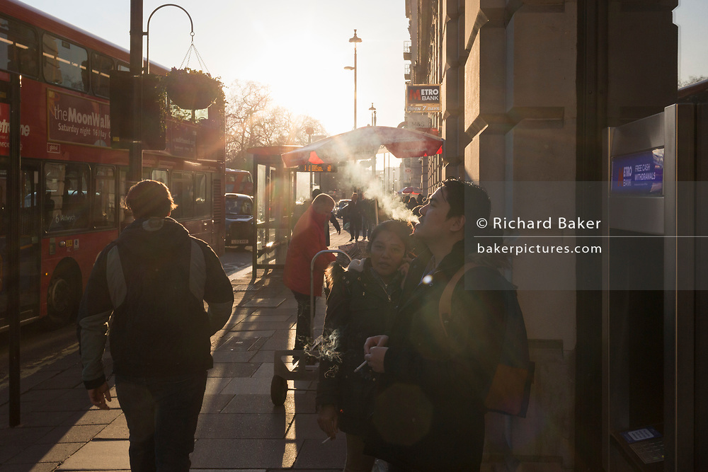A man exhales cigarette smoke in winter sunshine on Piccadilly, on 20th January 2020, in London, England.