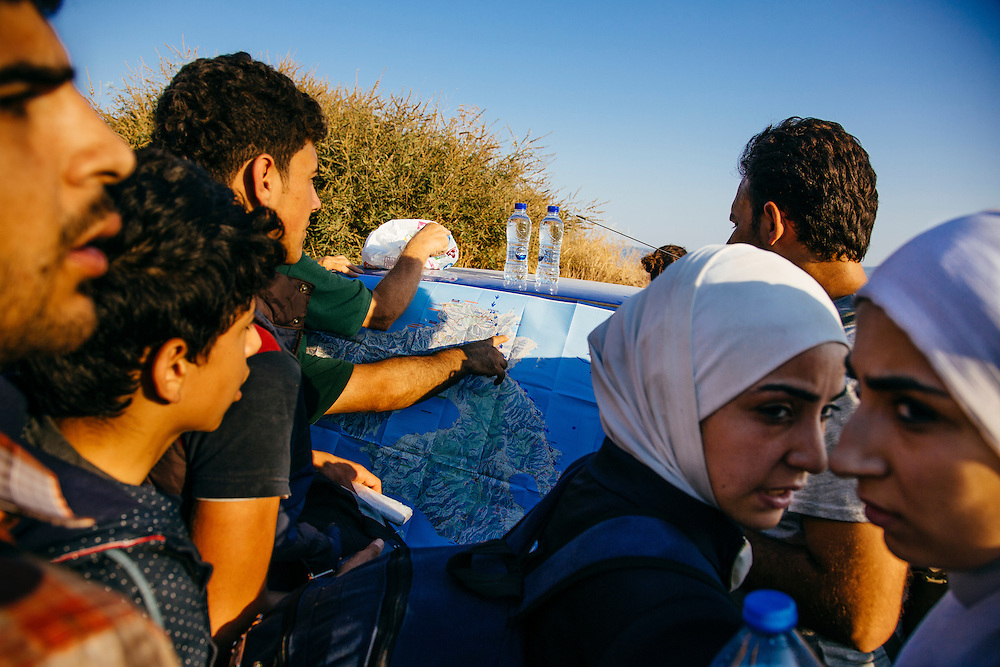 Refugees check out a route  on a map from where they arrived to the town of Mytilini where they take a ferry to Athens in Lesvos island, Greece on Aug 12, 2015. Mytilini is about 65km away from  Molyvos where many boats arrive.