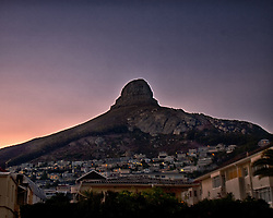 March 19, 2011 - Cape Town, Western Cape, South Africa - Silhouetted at dawn, Cape Town's celebrated geographical landmark Lion's Head crests at 669 m. (2,195 ft) above sea level. The peak forms part of a dramatic backdrop to the city of Cape Town and is part of the Table Mountain National Park. This view from suburban Sea Point. (Credit Image: © Arnold Drapkin/ZUMAPRESS.com)
