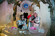 Yakutsk, Yakutia, Russia, 19/08/2011..Nikolai Dzhoi and his wife Ludmilla drink vodka and eat local raw fish inside the Permafrost Kingdom, an underground tourist attraction inspired by the extreme cold of Yakutia. The 150 metre deep complex of tunnels in the Russian permafrost are decorated with ice sculptures, a wolf-fur covered throne, an office complete with the coolest computer and telephone, a children's slide and other ingenious creations - all hewn from blocks of ice.