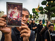 29 OCTOBER 2016 - BANGKOK, THAILAND: A man holds a picture of the Bhumibol Adulyadej, the King of Thailand, while he files into the Grand Palace to homage to the King. Saturday was the first day Thais could pay homage to the funeral urn of the late Bhumibol Adulyadej, King of Thailand, at Dusit Maha Prasart Throne Hall in the Grand Palace. The Palace said 10,000 people per day would be issued free tickerts to enter the Throne Hall but by late Saturday morning more than 100,000 people were in line and the palace scrapped plans to require mourners to get the free tickets. Traditionally, Thai Kings lay in state in their urns, but King Bhumibol Adulyadej is breaking with tradition. His urn reportedly contains some of his hair, but the King is in a coffin,  not in the urn. The laying in state will continue until at least January 2017 but may be extended.       PHOTO BY JACK KURTZ