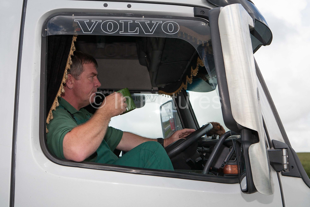 A lorry driver drinking a mug of tea whilst sitting in his cab, at Bodmin Moor layby along the A30, on 23rd June 2008 in Bodmin Moor in the United Kingdom.