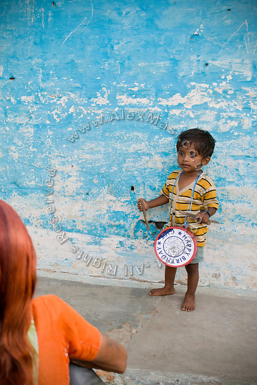 A young boy is playing a small drum near his home, in a water-contaminated colony of Bhopal, Madhya Pradesh, India, near the abandoned Union Carbide (now DOW Chemical) industrial complex, site of the infamous '1984 Gas Disaster'.