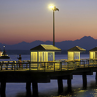 USA, Washington, Seattle, Angler fishes from dock along Pier 86 on Elliot Bay across from Olympic Mountains at dusk