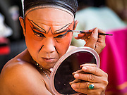 16 JANUARY 2015 - BANGKOK, THAILAND:  A performer with the Sai Yong Hong Teochew Opera Troupe puts on his make up before performing at the Chaomae Thapthim Shrine, a Chinese shrine in a working class neighborhood of Bangkok near the Chulalongkorn University campus. The troupe's nine night performance at the shrine is an annual tradition and is the start of the Lunar New Year celebrations in the neighborhood. Lunar New Year, also called Chinese New Year, is officially February 19 this year. Teochew opera is a form of Chinese opera that is popular in Thailand and Malaysia.   PHOTO BY JACK KURTZ