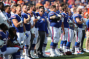Some Buffalo Bills players stand with their hands over their hearts while others kneel during the playing of the National Anthem before the 2017 NFL week 3 regular season football game against the against the Denver Broncos, Sunday, Sept. 24, 2017 in Orchard Park, N.Y. The Bills won the game 26-16. (©Paul Anthony Spinelli)