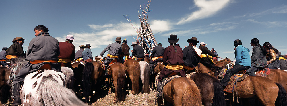 A group of horsemen outside of the town of Moron. They gather for a religious ceremony to listen to the Lamas recite Sutras, dialogues of the Buddha, to bless the area and bring a good omen for the year to come.