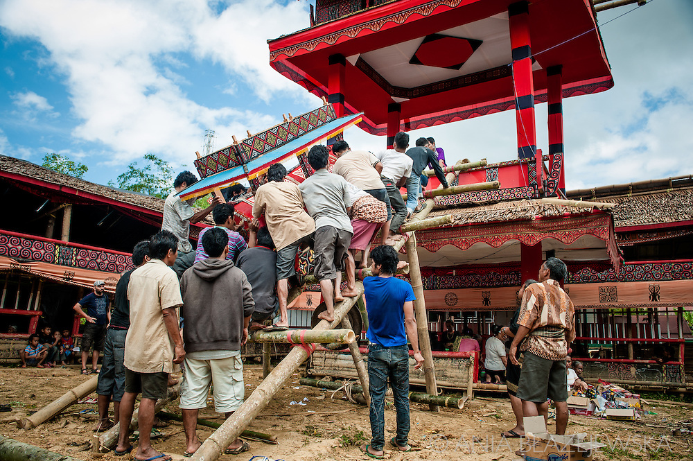 Indonesia, Sulawesi, Tana Toraja. A coffin with a body of a deceased is being put in a lokkian, a special funeral construction.<br />