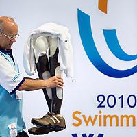 Nederland, Eindhoven, 19-08-2010.<br /> Zwemmen, Internationaal, IPC Swimming World Championships.<br /> Een medewerker brengt een paar prothesen van een deelnemer die aan het zwemmen is tijdens een finale naar de rand van het bad. <br /> Foto : Klaas Jan van der Weij