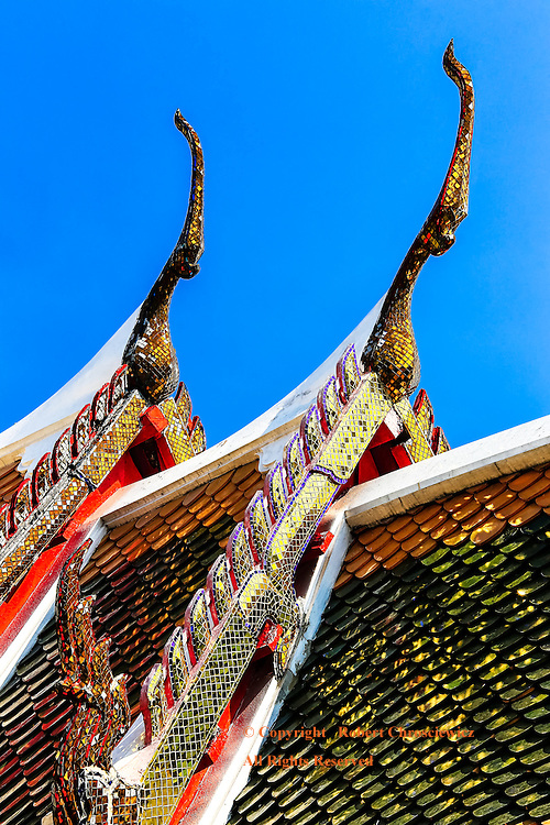 Intricate Chofa: Chofa crown an intricate roof top and the numerous bright colours are set against a clear blue sky, Wat Arun, Bangkok Thailand.