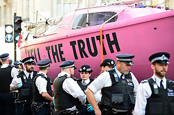 "© Licensed to London News Pictures. 19/04/2019. LONDON, UK.  Police officers form a cordon for the removal of the pink boat at Oxford Circus during ""London: International Rebellion"", on day five of a protest organised by Extinction Rebellion.  Protesters are demanding that governments take action against climate change.  Police have issued a section 14 order requiring protesters to convene at Marble Arch only so that the protest can continue.  Photo credit: Stephen Chung/LNP"