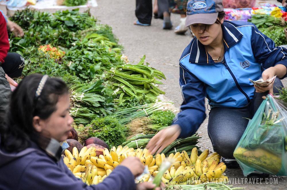 A customer buys a bunch of bananas at the morning market in Luang Prabang, Laos.