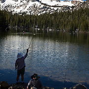 A slow start to summer in the Eastern Sierras as record snowfall carried over into the summer months. Fishermen enjoy the scenery while fishing Lake Mamie with Crystal Crag in the background