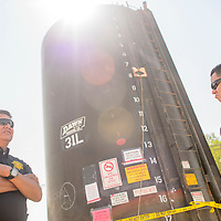081915       Cable Hoover<br /> <br /> Navajo Nation police investigators Alvernon Tsosie, left, and Jerrek Curley are posted at a water storage tank that has been taped off and marked as evidence Wednesday in Shiprock.