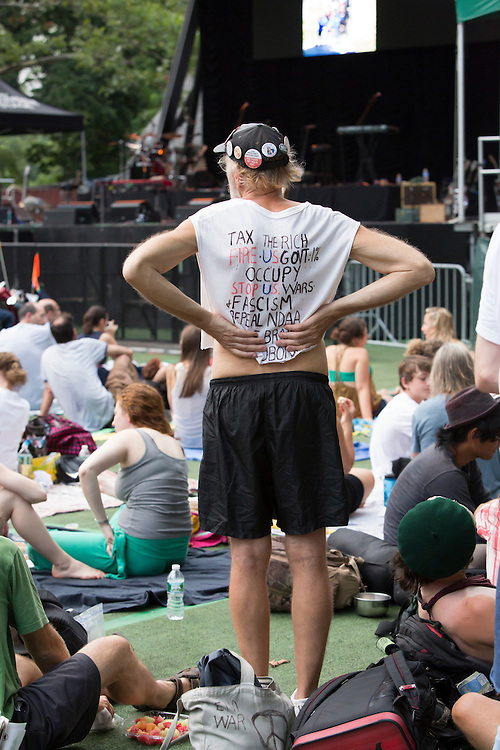 "A man from Occupy Wall Street in the audience, T-shirt hand-lettered with ""Tax the Rich"", ""Occupy"", and other slogans."
