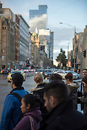 Pedestrians wait to cross the street outside Flinders Street Station in the Central Business District of Melbourne, Victoria