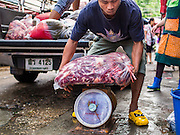 "05 APRIL 2014 - BANGKOK, THAILAND:   A delivery man brings pork offal into Khlong Toey Market in Bangkok. Khlong Toey (also called Khlong Toei) Market is one of the largest ""wet markets"" in Thailand. The market is located in the midst of one of Bangkok's largest slum areas and close to the city's original deep water port. Thousands of people live in the neighboring slum area. Thousands more shop in the sprawling market for fresh fruits and vegetables as well meat, fish and poultry.     PHOTO BY JACK KURTZ"