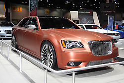 """08  February 2013: Chrysler 300S Turbine concept car. Chicago Auto Show, Chicago Automobile Trade Association (CATA), McCormick Place, Chicago Illinois<br /> <br /> 2013 CHRYSLER 300 SRT8: Not for the faint-of-heart, the 2013 Chrysler 300 SRT8 sedan is for drivers that seek adrenaline-filled excitement, but don't want to sacrifice comfort and innovative features to get it. With head turning designs inside and out, the 300 SRT8 provides the ultimate combination of world-class luxury, power and handling. Under the hood of the '13 Chrysler 300 SRT8 roars the might 6.4-liter Hemi V-8 engine that delivers 470 horsepower to the rear wheels. Incredible performance numbers like 0-60 mph acceleration in the high 4-second range and top speed of 175 mph backup the vehicles """"muscular"""" appearance. The 300 SRT8 also sports impressive stopping power - 60-0 mph in 120 feet, thanks to the 14.2 inch (front) and 13.8 inch (rear) vented/slotted rotors with four-piston Brembo calipers painted in silver finish. The return of the 300 SRT8 to the Chrysler lineup in 2012 has been a success, and for 2013, the modern muscle car continues to sit a half inch lower than not-SRT models. It also wears black chrome upper and lower grille surrounds, rear valance strip, and standard seven-spoke, 20-inch, fully forged aluminum with polished face and painted sparkle silver. Around back, the rear includes a unique lower fascia with chrome accent bar, four-inch round dual exhaust tips and a modified SRT8 deck-lid badge with black accent. The racing-inspired five-passenger cabin includes a leather-wrapped, heated, SRT-exclusive steering wheel with a flattened bottom surface, real carbon fiber interior trim pieces, plus, racing style brake and gas pedal pads. Nine exterior colors for 2013 include shades with names such as, Deep Cherry Red Pearl Coat, Jazz Blue Pearl Coat and Phantom Black Tri-coat Pearl."""