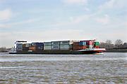 Nederland, Dodewaard, 14-2-2019Een binnenvaartschip vaart over de Waal beladen met containers richting Rotterdam Foto: Flip Franssen.