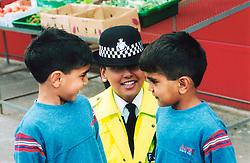 Female police officer talking to children; Bradford; Yorkshire UK