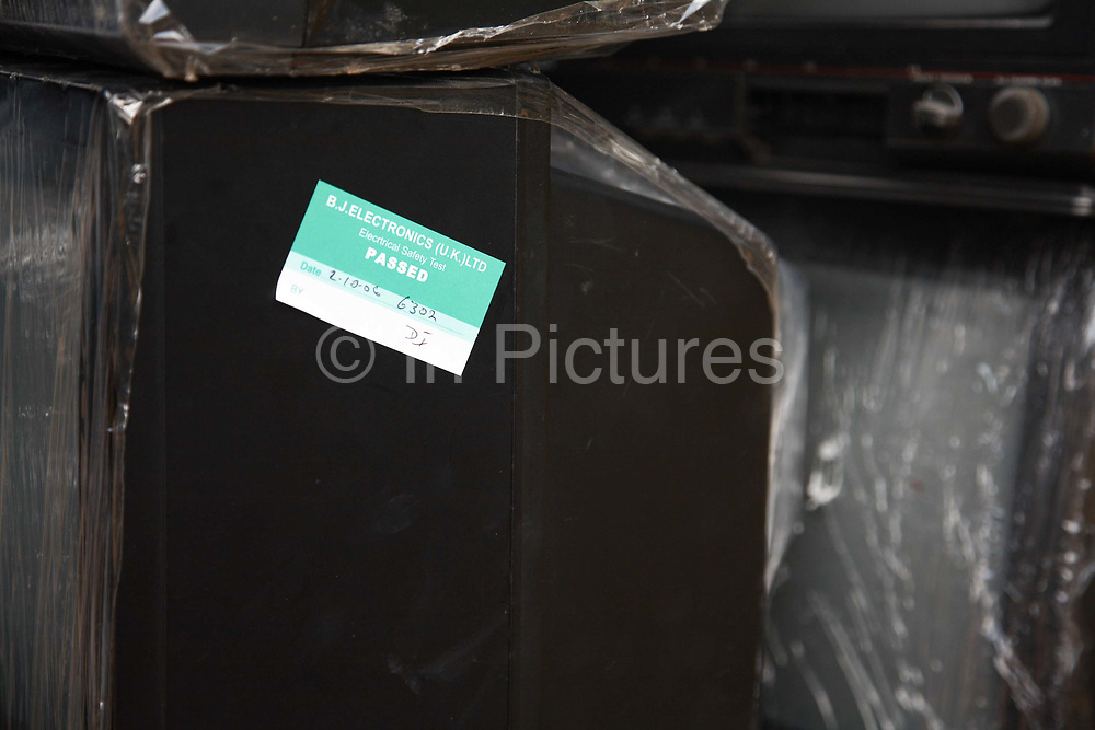 A sticker claiming this particular TV was tested and passed by B>J>Electronics in the UK. This picture is part of an undercover investigation by Greenpeace and Sky News.  A TV-set originally delivered to a municipality-run collecting point in UK for discarded electronic products was tracked and monitored by Greenpeace using a combination of GPS, GSM, and an onboard radiofrequency transmitter placed inside the TV-set.  The TV arrived in Lagos in container no 4629416 and was found in Alaba International Market and bought back by Greenpeace activist. The TV was subsequently brought back to England and used as proof of illegal export of electronic waste. A number of individual are currently on trial in London in connection with illegal exports(Nov 2011)