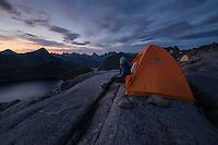 Female hiker sits in from of tent under last twilight light in late summer near summit of Moldtind, Moskenesøy, Lofoten Islands, Norway